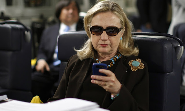 Then-secretary of state Hillary Clinton using her smartphone onboard a C-17 military plane. Photograph: Kevin Lamarque/AP