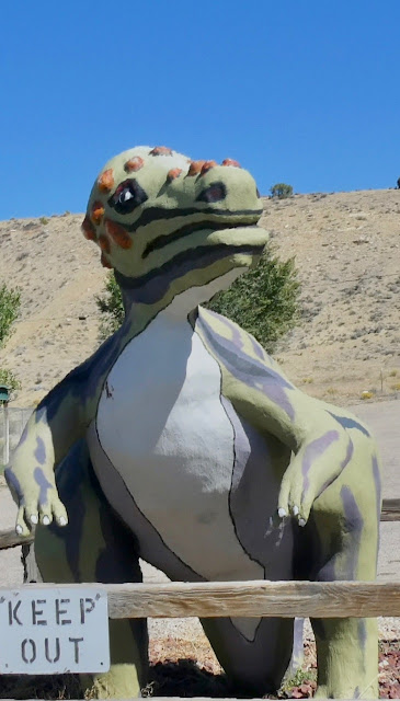 Cartoon-like dinosaur statue against an arid hillside