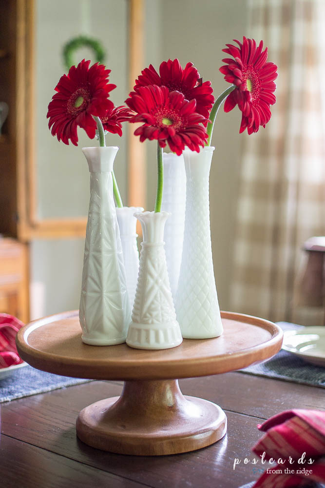 red flowers in milk glass vases on a wood pedestal