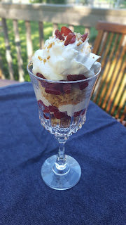 strawberries, whipped cream and biscuit crumbles in a tall glass