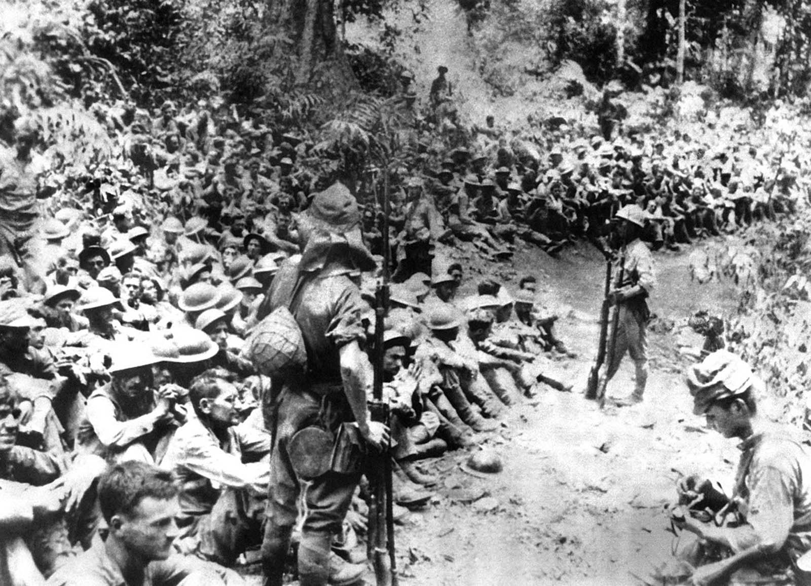 Japanese soldiers stand guard over American war prisoners just before the start of the