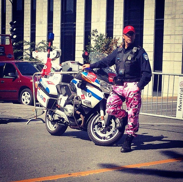 Montreal Police Officer stands by his motorcycle, in uniform except for pink camo pants. Police Pants Protest. marchmatron.com