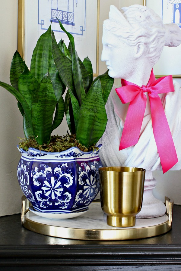 snake plant, round marble and brass tray, lady bust, island moonlight candle