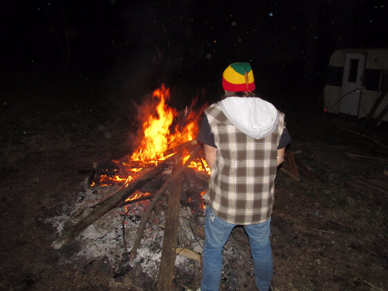 Grunge dude is pissing on a campfire. Can't see his dick, though.