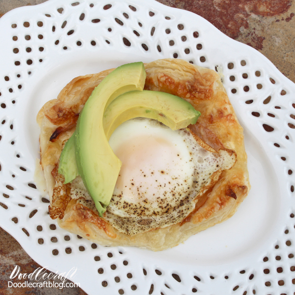 Crisp puff pastry with ham and cheese, topped with a fried egg and sliced avocado for a delicious croque madame