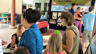 Kids and parents talking to a Camp representative who is exhibiting her camp program at L.A. Camp Fair 2018