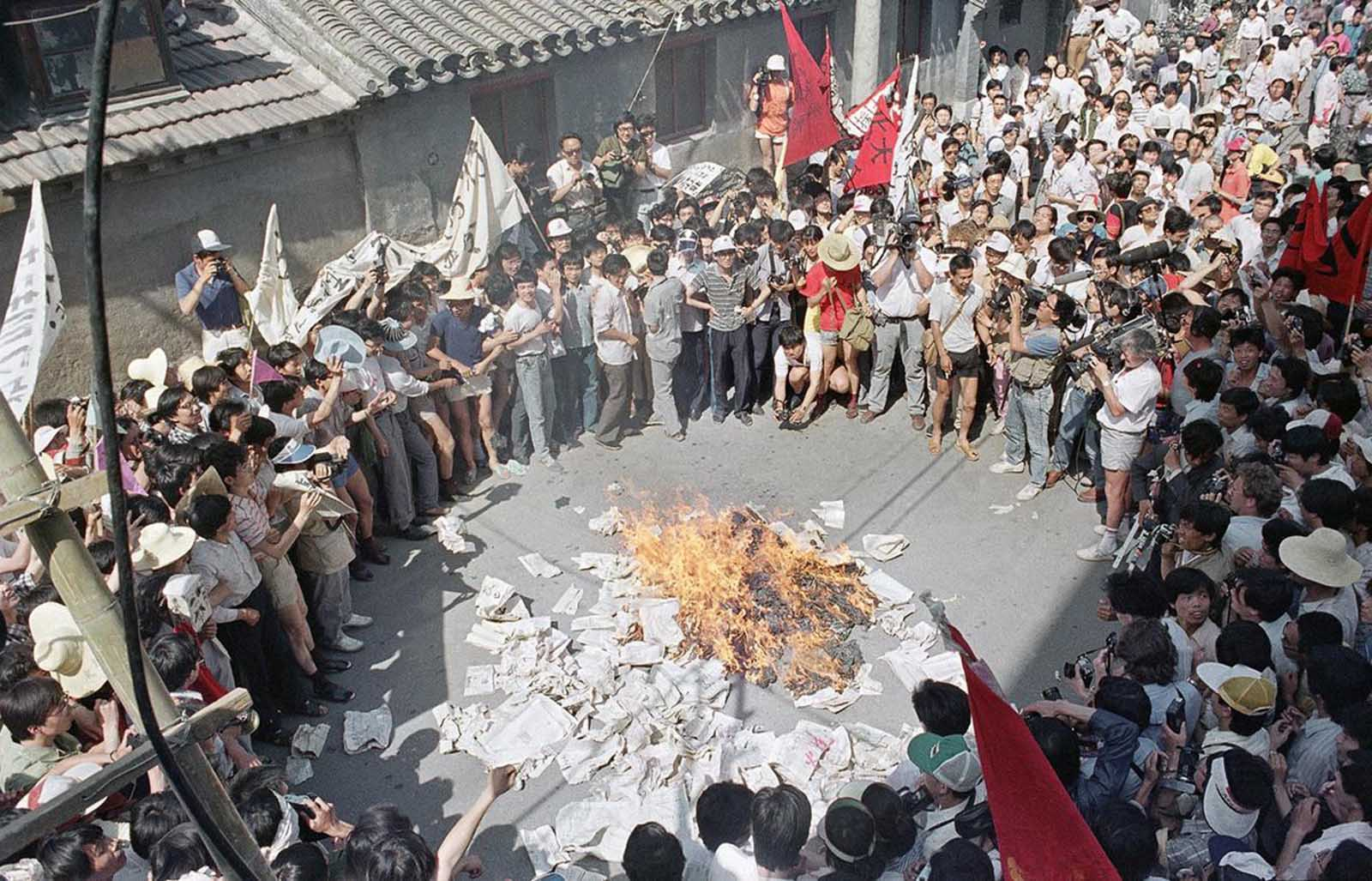 A huge crowd gathers to watch as student protestors burn copies of the Beijing Daily in retaliation for anti-student articles in front of the newspaper's offices, on June 2, 1989.
