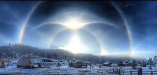 O fenômeno atmosférico Parahelio é produzido pelo reflexo da luz do sol, e acontece quando a luz solar incide sobre um conjunto de cristais de gelo na atmosfera ao redor das nuvens, estes cristais atuam como prismas e espelhos através dos quais a luz passa e é refletida formando os Parahelios.  Foto em um vilarejo nevado. No céu em tons de azul claro/escuro, desenhos circulares que remetem à mandalas, delineadas por arco-íris refletem raios luminosos em diferentes intensidades.