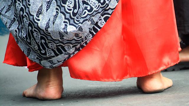 Kuatnya kaki penari payung menahan panas dari aspal walau tanpa alas kaki.