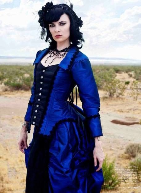 woman wearing gothic victorian blue and black gown (bodice and skirt) with black fascinator and victorian necklace