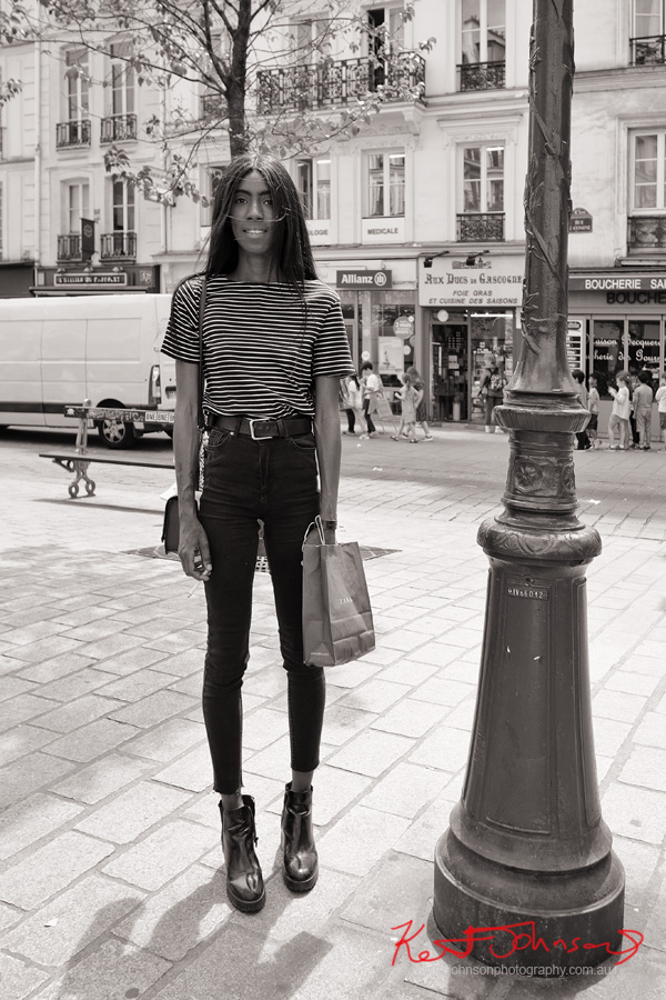 Young woman wearing a striped tee shirt and tight black jeans and ankle boots, Le Marais, Rue Saint-Antoine, Paris. Photographed by Kent Johnson for Street Fashion Sydney.