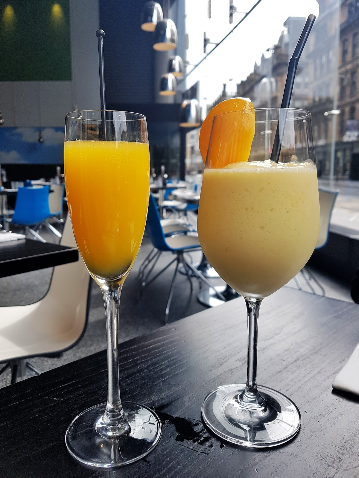Close up of two CAU Cocktails. One Peaches and cream and one Mimosas