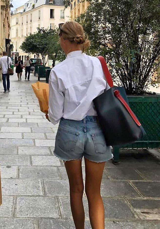 A Stylish Way to Wear Cut-Off Denim Shorts — Amalie Moosgaard Neilsen in Summer Outfit on Instagram White Button-Down Shirt, Cut-Off Jean Shorts, Gold Jewelry, and Celine Tote Bag