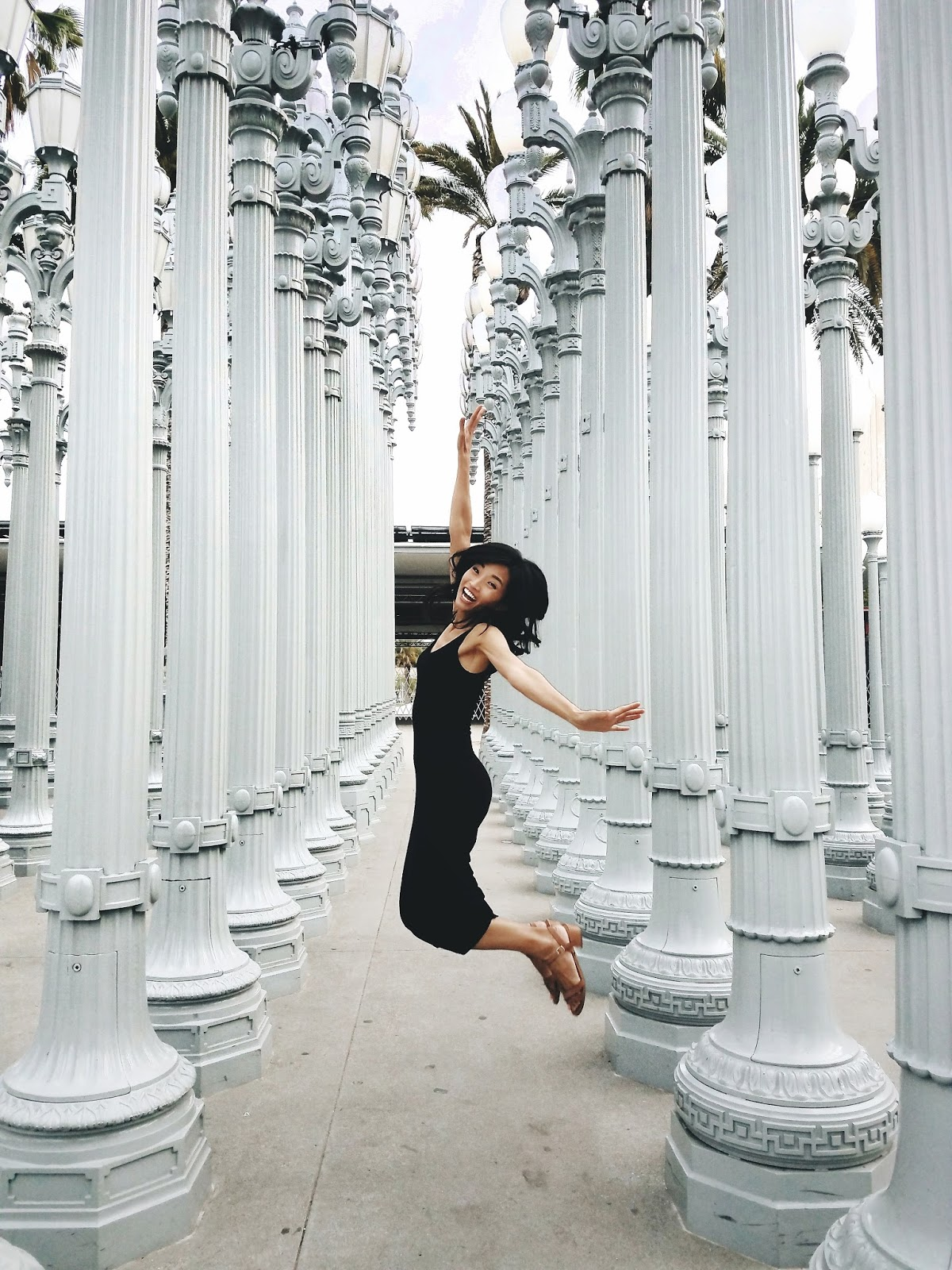 The Jen Project's Jen playing tourist at LACMA, jumping in front of the Urban Lights exhibit.