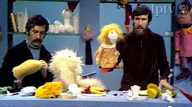 Don Sahlin, with think black hair and mustache, and Jim Henson, with brown hair and long scruffy beard, creating puppets from various materials on table before them