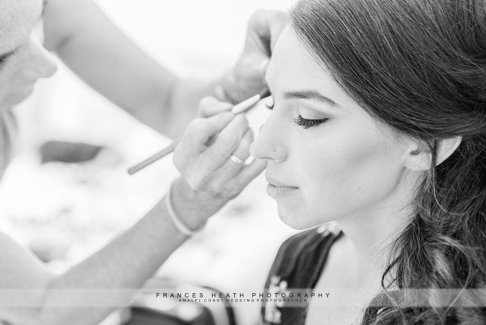 Bride having make-up done on her wedding day