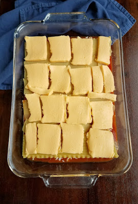 lasagna noodles with slices of american cheese on them, middle layer of lasagna