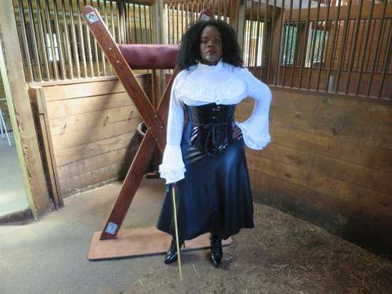 mistress with black frock, holding a cane in the stables.