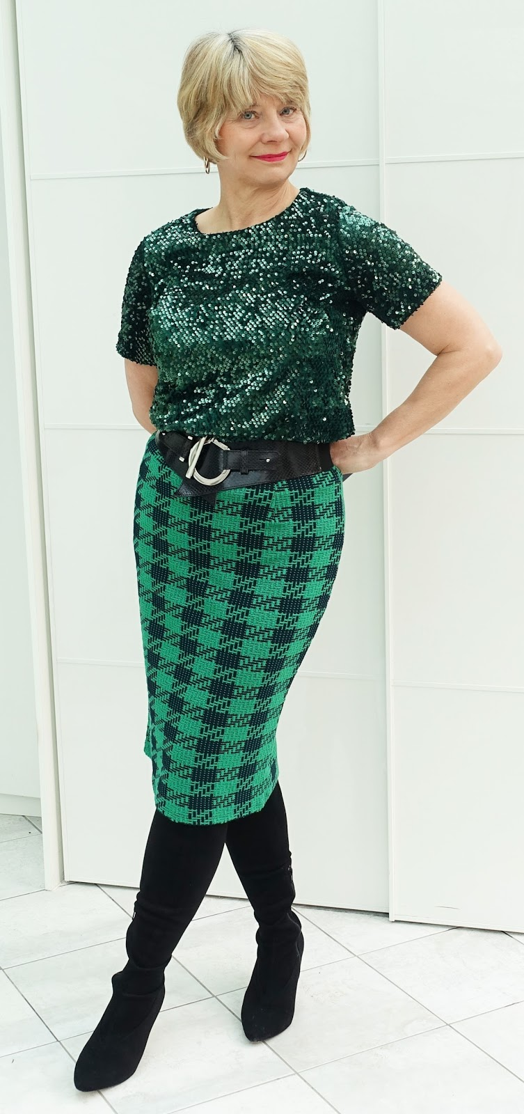 Image showing over 45s blogger Gail Hanlon wearing sequins for the daytime.  A green sequin top is worn with a green and black skirt, wide black belt and black boots.