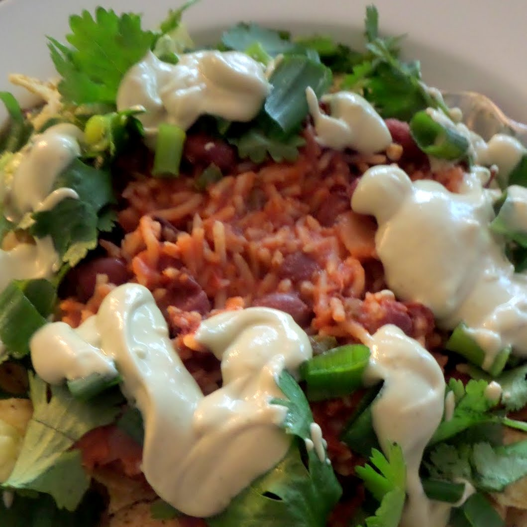 Bean and Rice Taco Salad:  A vegetarian meal of tortilla chips and lettuce, topped with spicy rice and beans, and finished with avocado sour cream and cilantro.