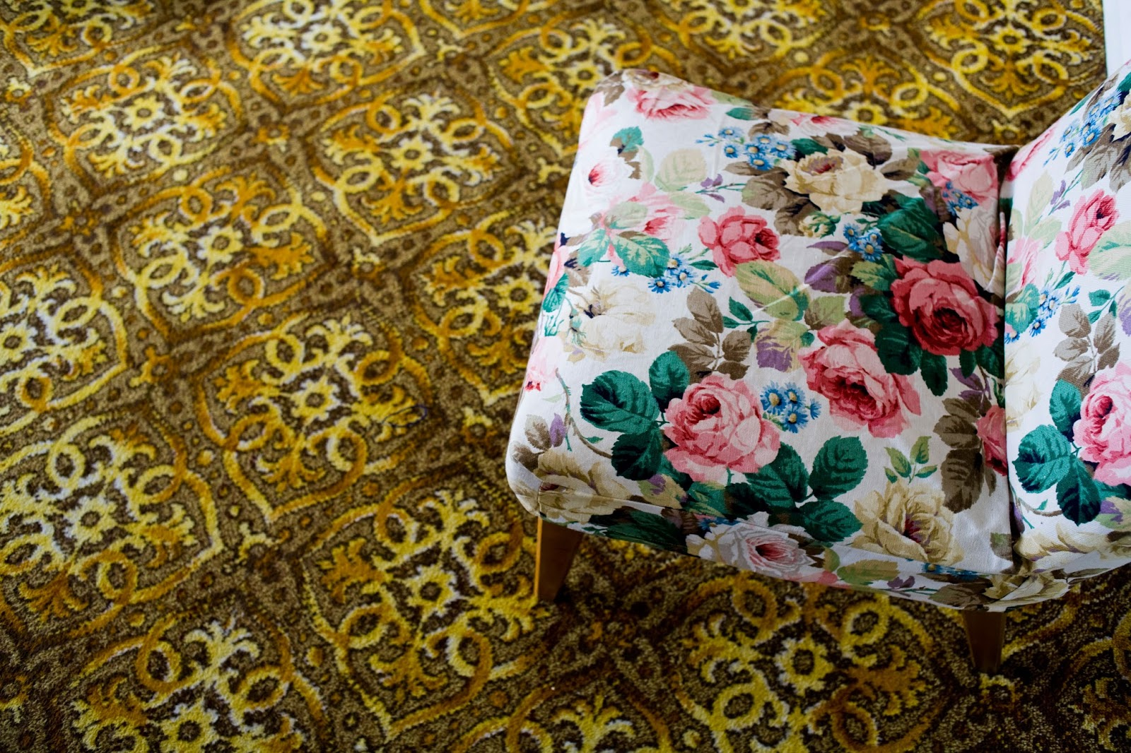 Floral patterned chair on heavily patterned carpet