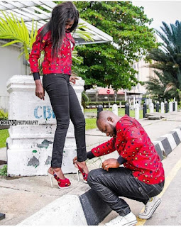 Man Helps His Fiancée Adjust Her Shoes In Matching Outfits Pre-Wedding Photos