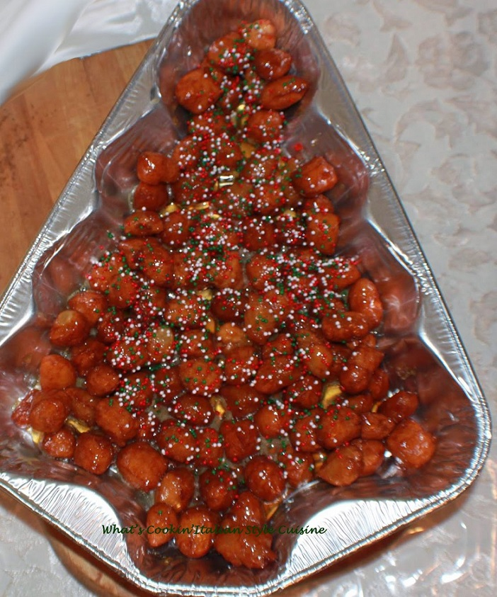 this is how to make Italian honey balls called struffoli at Christmas, this is an old Italian tradition that has a fried cookie dough and honey on them with little colored candy balls on top in a christmas shaped foil tin.
