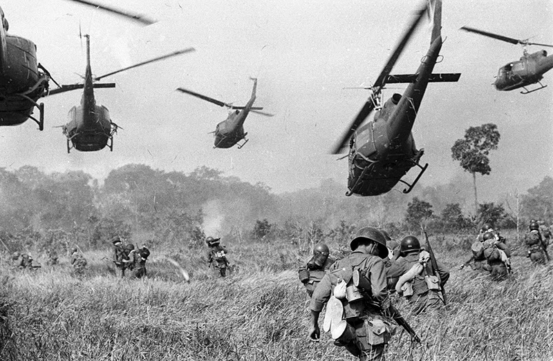 Hovering u s army helicopters pour machine gun fire into a tree line to cover the advance of south vietnamese ground troops in an attack on a viet cong