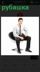 Молодой человек сидит в темном кресле в рубашке и галстуке с улыбкой на лице, в черных ботинках