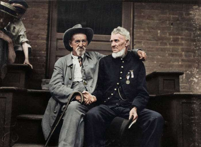 Colorized photo of Civil War Veterans, North and South, sit on the front steps and shake hands