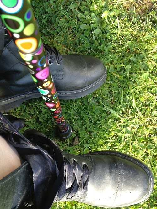 Self-taken photo of person's feet in dusty black boots, with end of multicolored cane between them