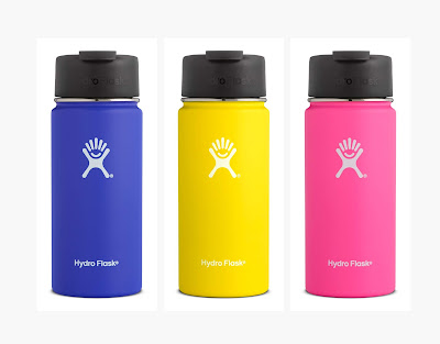 A row of three Hydroflask coffee flasks in Blueberry, Lemon and Pink.