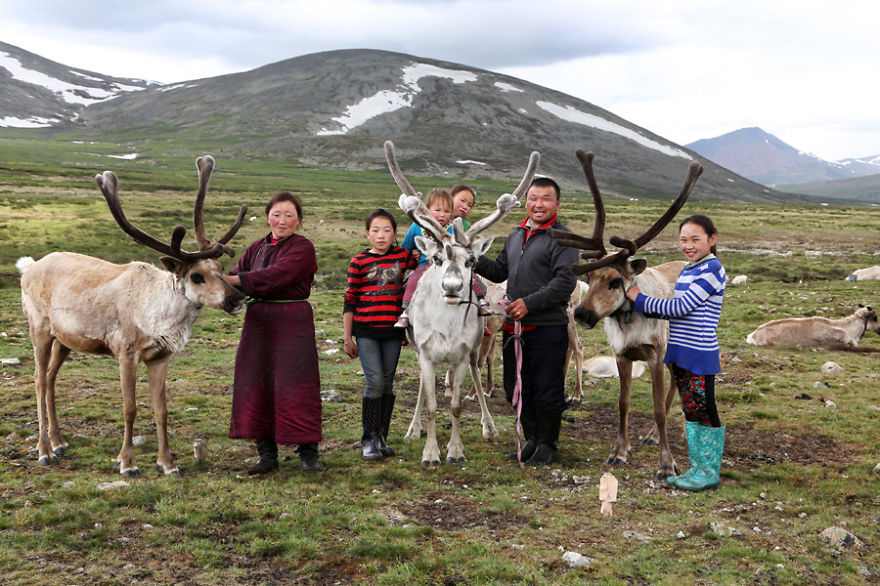 Full family posing proudly with some of their reindeer - Meet The Tsaatan Nomads In Mongolia Who Live Like No One Else