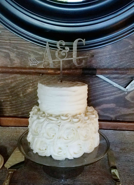 wedding cake with 1 large layer and 1 small layer. Rosettes on bottom and subtle ruffle on top layer in frosting