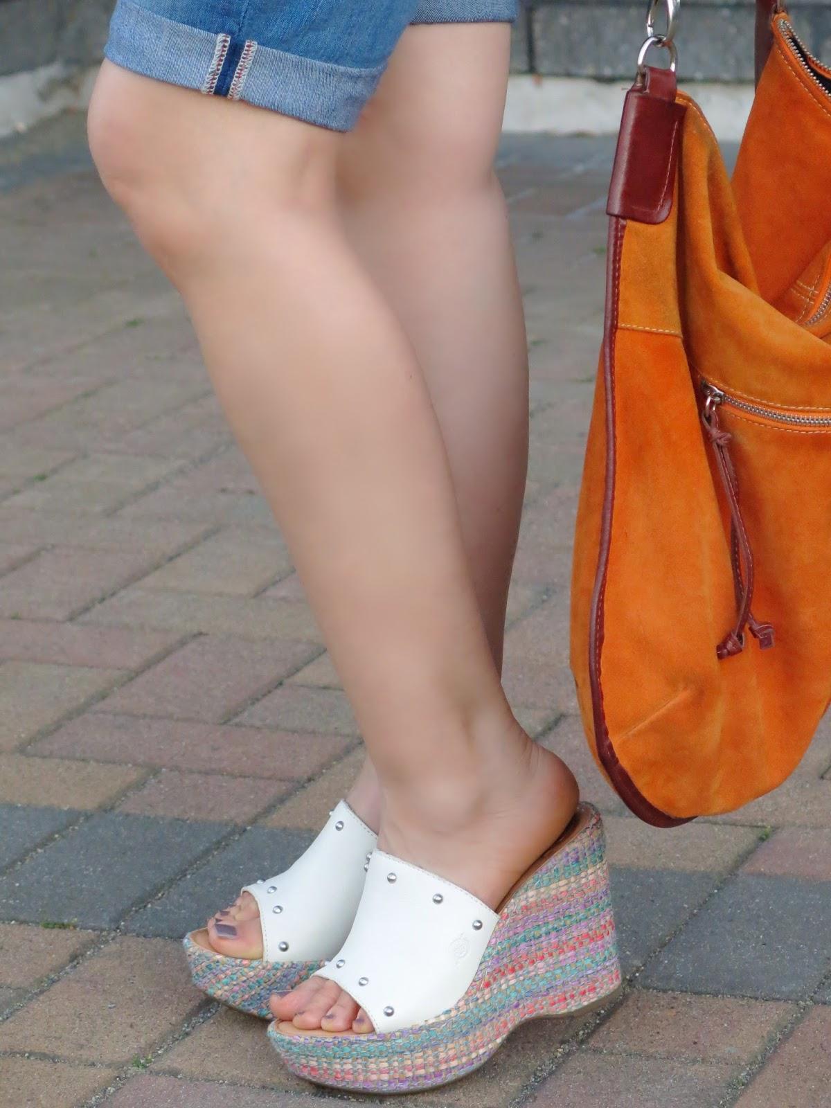 denim bermuda shorts, platform wedges, and orange suede bag