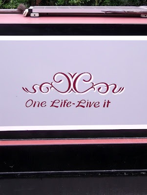 "Image of signwriting on a narrow boat reading ""one life live it"""