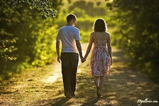 Ζευγάρι περπατούν πιασμένοι χέρι χέρι στην εξοχή.