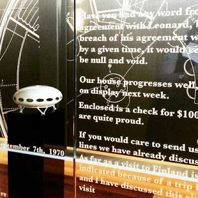 Model of a Futuro House in front of a wall of sketches of its design and behind a window covered with replicas of original correspondence about the company.