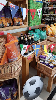 M & S display with an image of a football and bunting representing the flags of different countries. There are no words, just chips and alcohol.