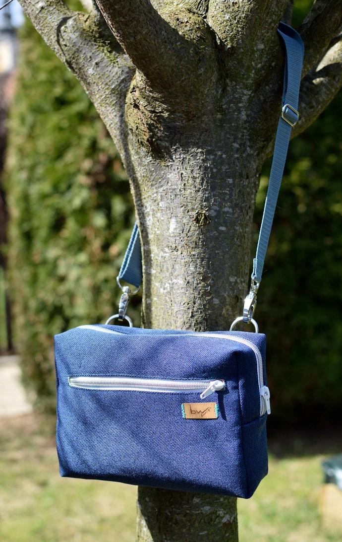 Hüfttasche an einem Baum hängend, mit der Tragevariante als Umhängetasche