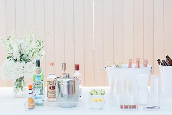 imagen_primer_cumpleaños_casa_blanco_mesa_bar_bebidas_flores