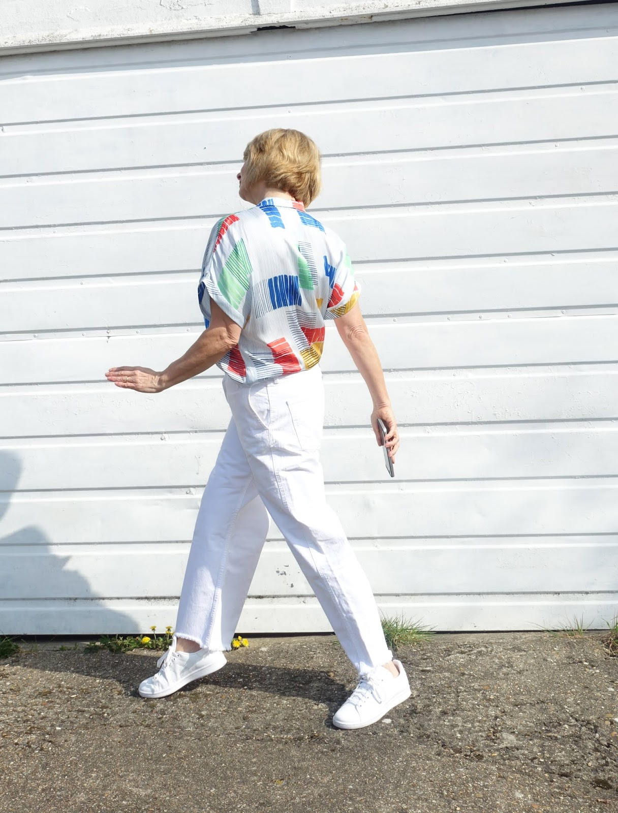 Side view of blonde woman in white frayed edge wide leg jeans and geometric print blouse by Esprit with white Stan Smith trainers