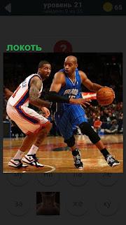 В баскетболе противник локтем отталкивает соперника с мячом