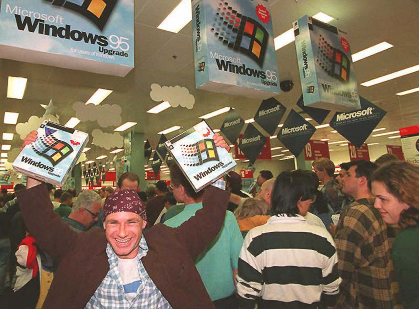 Mikol Furneaux waves two copies of Windows 95 at a midnight launch at a store in Sydney, Australia.