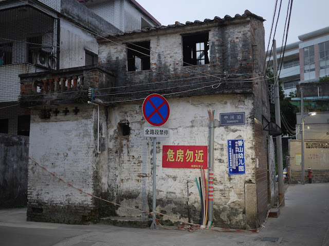 "house with ""危房勿近"" sign on it"