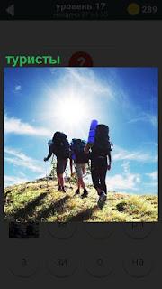 Под ярким солнцем идут туристы с рюкзаками, друг за другом