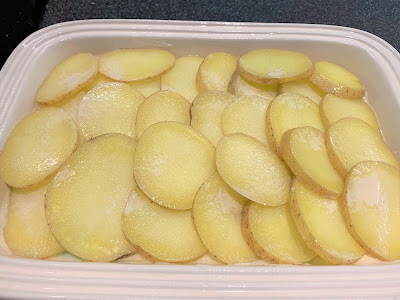 Sliced potatoes on top of chicken bake in a cream coloured casserole dish.