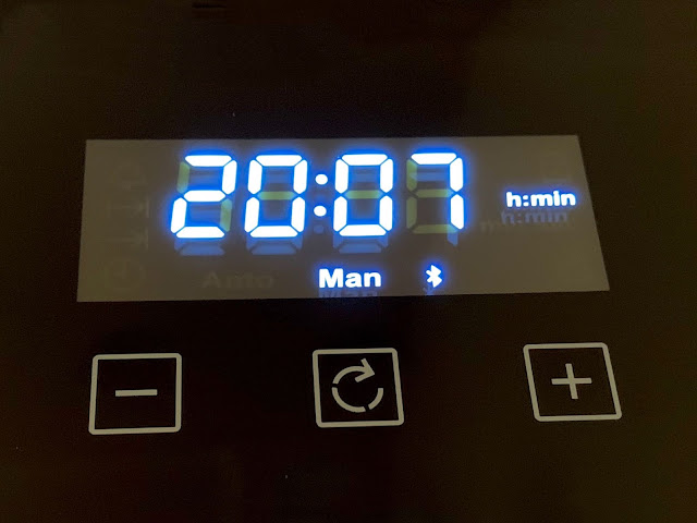 A bright white LED clock with Man (manual) and bluetooth symbol