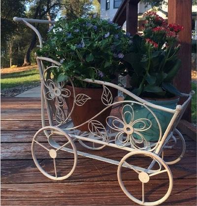 Manfaatkan troli atau kereta bayi yang sudah rusak untuk memajang vas atau pot bunga hias di teras rumah