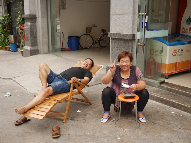 man resting on an outdoor lounge chair and woman posing for a photograph